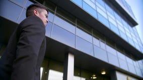 Hombre de negocios atractivo y confiado que camina cerca del edificio de oficinas moderno metrajes