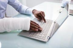 Hombre de negocios With Bandage Hand usando el ordenador portátil fotos de archivo