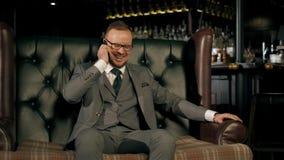 Hombre de negocios barbudo acertado en un traje que se sienta en un sofá de cuero lujoso, hablando en el teléfono y disfrutando d almacen de video