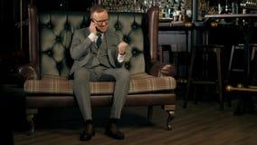 Hombre de negocios barbudo acertado en un traje que se sienta en un sofá de cuero lujoso, hablando en el teléfono y disfrutando d metrajes