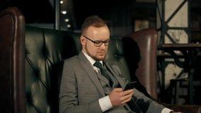 Hombre de negocios barbudo acertado en un traje que se sienta en un sofá de cuero lujoso y que mira al teléfono cantidad 4k almacen de video