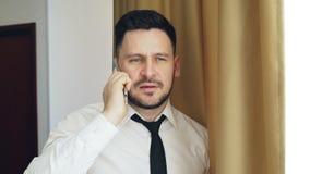 Hombre de negocios barbudo adulto en la camisa blanca y lazo que hablan en el teléfono móvil que coloca la ventana cercana en la  metrajes