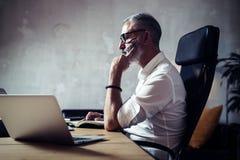 Hombre de negocios barbudo adulto que lleva los vidrios clásicos y que trabaja en la tabla de madera en desván moderno Horizontal Imagen de archivo libre de regalías
