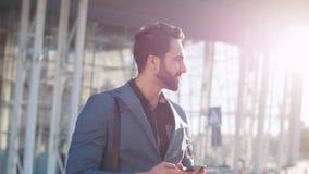 Hombre de negocios barbudo atractivo que mira alrededor y que usa su smartphone mientras que sale del edificio vidrioso moderno almacen de video