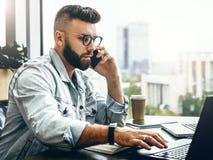 Hombre de negocios barbudo, blogger que se sienta en café, hablando en el teléfono elegante, trabajando en el ordenador portátil, imagen de archivo