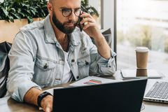 Hombre de negocios barbudo, blogger que se sienta en café, hablando en el teléfono elegante, trabajando en el ordenador portátil, foto de archivo