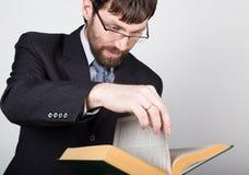 Hombre de negocios barbudo en un traje de negocios y un lazo, leyendo un libro grueso Imagen de archivo