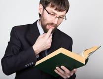 Hombre de negocios barbudo en un traje de negocios y un lazo, leyendo un libro grueso Fotos de archivo