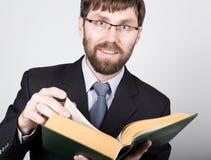 Hombre de negocios barbudo en un traje de negocios y un lazo, leyendo un libro grueso Imagen de archivo libre de regalías