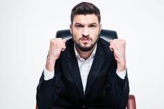 Hombre de negocios barbudo enfadado enojado que sienta y que muestra los puños imagen de archivo