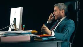 Hombre de negocios barbudo enojado que tiene conversación agotadora emocional sobre su teléfono celular Fondo negro Foto de archivo