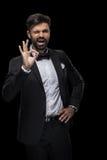Hombre de negocios barbudo hermoso en corbata de lazo que guiña y que muestra la muestra aceptable Foto de archivo libre de regalías
