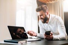 Hombre de negocios barbudo joven en la camisa blanca que se sienta en la tabla delante del ordenador, mostrando la pluma en la pa fotografía de archivo libre de regalías