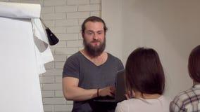 Hombre de negocios barbudo joven que lleva una reunión con los colegas en la oficina almacen de video