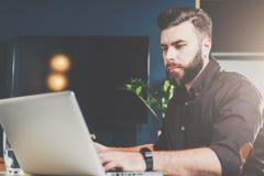Hombre de negocios barbudo joven que se sienta en oficina en la tabla y que trabaja en el ordenador portátil Hombre blogging, cha fotografía de archivo
