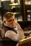 hombre de negocios barbudo mayor que mira la cámara mientras que se sienta en la tabla con el ordenador portátil foto de archivo