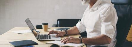 Hombre de negocios barbudo positivo usando el ordenador portátil móvil mientras que se sienta en la tabla de madera en el lugar c imágenes de archivo libres de regalías