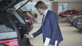 Hombre de negocios barbudo que elige el coche en cierre del salón del automóvil para arriba La tableta alta de la tenencia del ho almacen de video