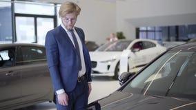 Hombre de negocios barbudo que elige el coche en cierre de la representación para arriba Hombre alto que mira el coche negro y qu metrajes
