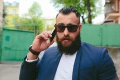 Hombre de negocios barbudo que mira el teléfono Imagen de archivo