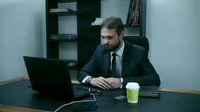 Hombre de negocios barbudo que se sienta en la oficina en el ordenador portátil, cámara lenta ultrajada, masculina almacen de video