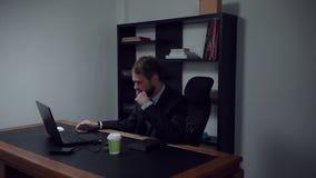 Hombre de negocios barbudo que se sienta en la oficina, películas de observación del trabajador de sexo masculino en el teléfono  almacen de video