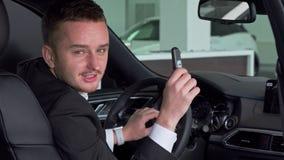 Hombre de negocios barbudo que sostiene hacia fuera el coche dominante a la cámara, sentándose en nuevo automóvil almacen de video