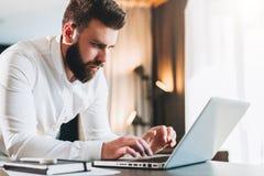 Hombre de negocios barbudo serio joven que se coloca en oficina cerca de la tabla y que usa el ordenador portátil El hombre traba fotos de archivo