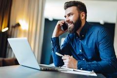 Hombre de negocios barbudo sonriente de los jóvenes que se sienta delante del ordenador, hablando en el teléfono celular, pluma d foto de archivo libre de regalías