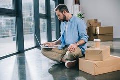 hombre de negocios barbudo usando el ordenador portátil mientras que se sienta en piso fotografía de archivo libre de regalías