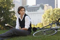 Hombre de negocios With Book Sitting en bicicleta en parque Foto de archivo libre de regalías