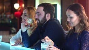 Hombre de negocios borracho, cansado que se sienta en el contador en barra con dos mujeres jovenes almacen de metraje de vídeo