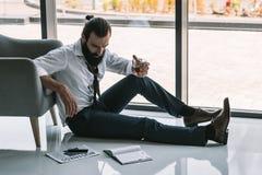 Hombre de negocios borracho que se sienta en piso imágenes de archivo libres de regalías