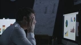 Hombre de negocios de bostezo que trabaja tarde en oficina de la noche almacen de metraje de vídeo