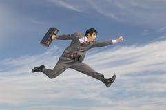 Hombre de negocios With Briefcase Running contra el cielo nublado Imagen de archivo libre de regalías