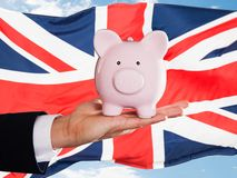 Hombre de negocios británico que lleva a cabo el piggybank Foto de archivo