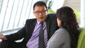 Hombre de negocios And Businesswomen Talking en el sofá almacen de metraje de vídeo