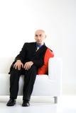 Hombre de negocios calvo en silla imagenes de archivo