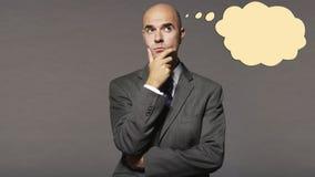 Hombre de negocios calvo que piensa con la burbuja del discurso sobre fondo gris Imagen de archivo libre de regalías