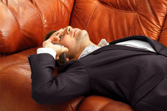Hombre de negocios cansado con el teléfono que miente en el sofá foto de archivo