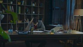 Hombre de negocios cansado en el final del día del trabajo en el estudio casero Hombre cansado que se sienta en el escritorio almacen de video