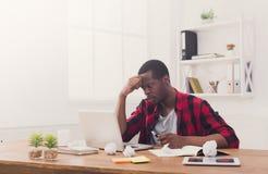 Hombre de negocios cansado negro en la oficina casual, trabajo con el ordenador portátil Imagen de archivo libre de regalías