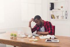 Hombre de negocios cansado negro en la oficina casual, trabajo con el ordenador portátil Fotografía de archivo libre de regalías
