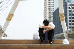 Hombre de negocios cansado o agotador que se sienta tristemente en las escaleras después de trabajar Fotografía de archivo