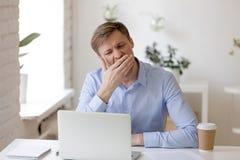 Hombre de negocios cansado que bosteza en el lugar de trabajo cerca del ordenador portátil imagenes de archivo
