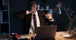 Hombre de negocios cansado que bosteza en la oficina de la noche