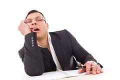 Hombre de negocios cansado que duerme en el trabajo que bosteza Foto de archivo libre de regalías