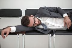 Hombre de negocios cansado que duerme en sillas en el vestíbulo de la oficina imagen de archivo libre de regalías