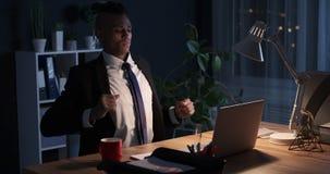 Hombre de negocios cansado que estira y que trabaja en el ordenador portátil en noche