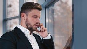 Hombre de negocios cansado que habla en un teléfono celular metrajes